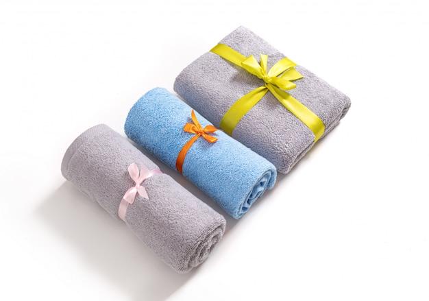 Tre asciugamani di spugna arrotolati e piegati legati da nastro rosa, arancione e giallo isolato. pila di asciugamani di spugna blu e grigi contro uno sfondo bianco.