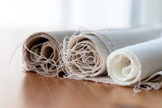 Tre rotoli di tessuto di lino naturale in diversi colori con fili sporgenti su un tavolo di legno.
