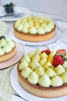 Tre rotonde di pasta frolla con crema di pistacchi verdi e marmellata di fragole vicino alla finestra