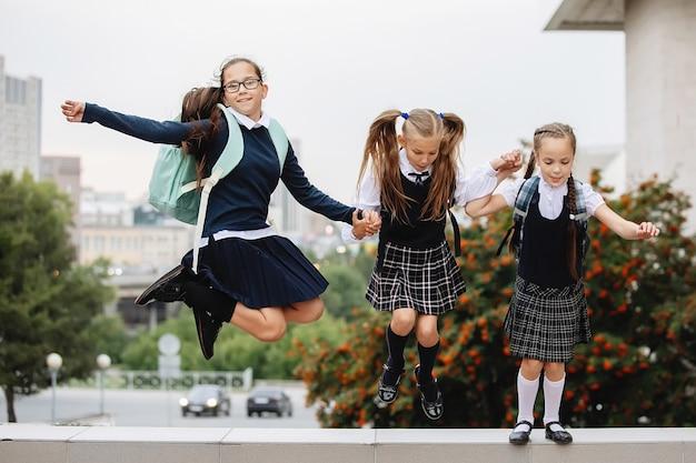 Tre studentesse in uniforme saltarono e ridono.