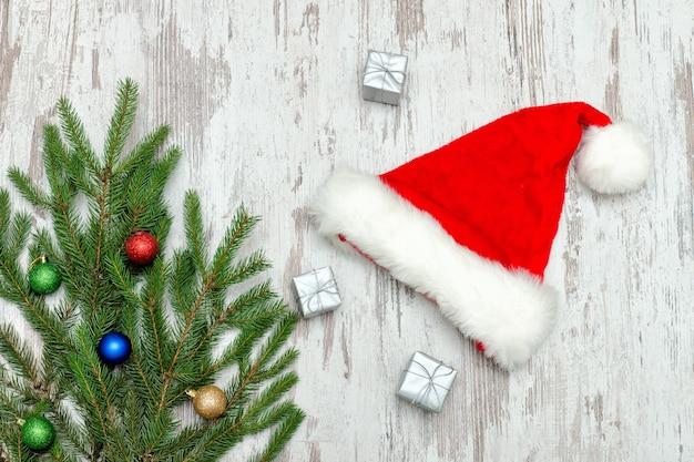 Tre scatole regalo argentate, decorate con un albero di natale e un cappello da babbo natale. sfondo in legno