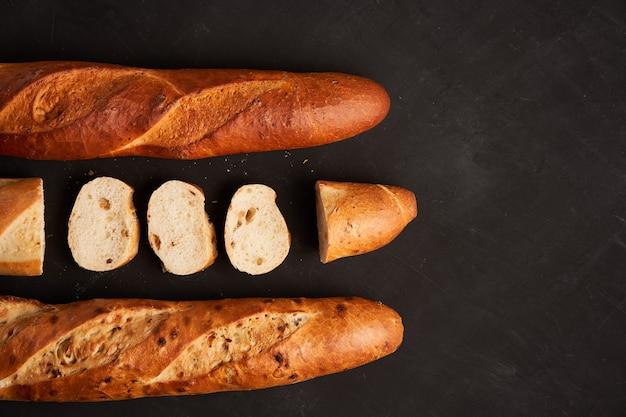 Tre baguette francesi croccanti affettate si trovano sullo sfondo del tavolo nero scuro semi di sesamo pasticcini nazionali francesi classici