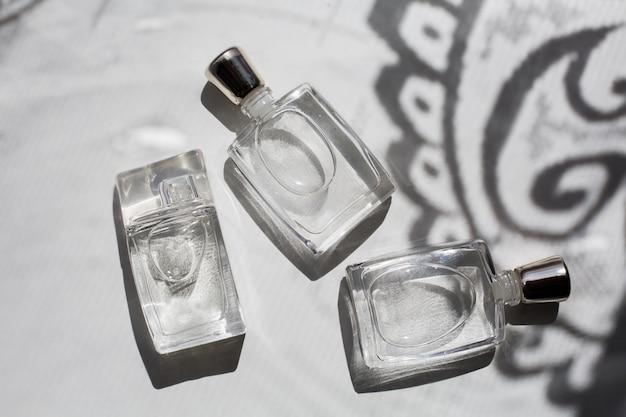 Tre piccole bottiglie di profumo in grigio