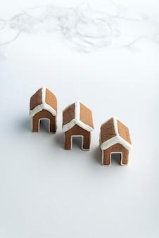 Tre piccole case di marzapane su sfondo bianco. prodotti da forno di natale.