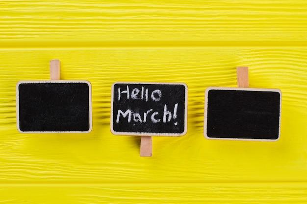 Tre piccole targhette su un tavolo di legno giallo. ciao concetto di marzo.