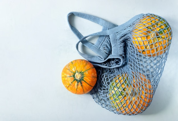 Tre piccole belle zucche mature giacciono in un sacchetto di corda ecologico grigio su grigio