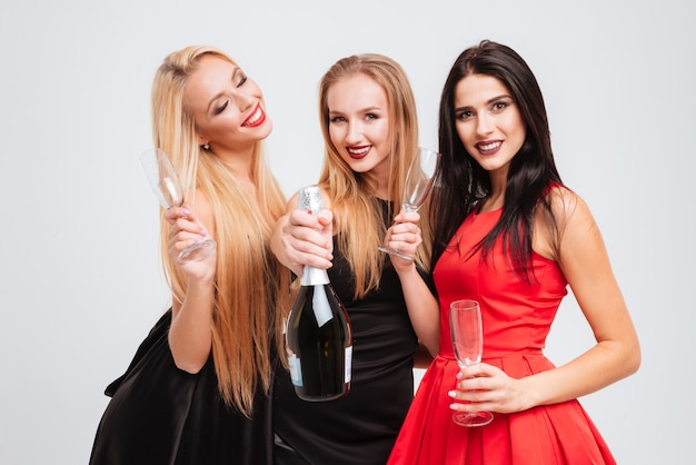 Tre giovani donne attraenti sorridenti che bevono champagne insieme su sfondo bianco