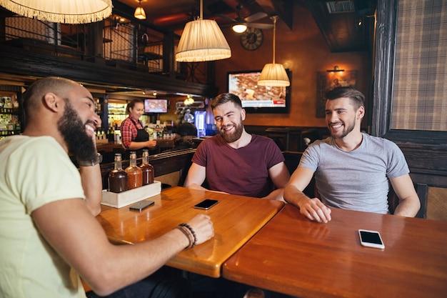 Tre amici maschi sorridenti seduti al ristorante