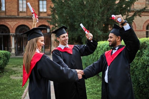 Tre compagni di classe laureati multinazionali sorridenti che salutano nel campus universitario in abiti di laurea con diploma.