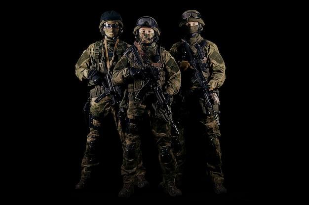 Tre soldati in uniforme con un'arma in mano guardano minacciosi. tecnica mista