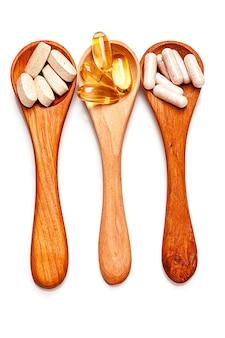 Tre cucchiai con olio di pesce e multivitaminici isolati su bianco