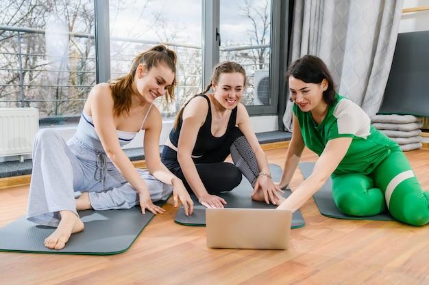 Tre ragazze sportive si siedono su stuoie in palestra durante i tutorial di allenamento yoga online