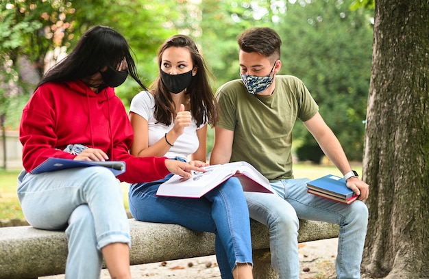 Tre studenti che studiano insieme seduti su una panchina all'aperto e indossano maschere durante il periodo del coronavirus