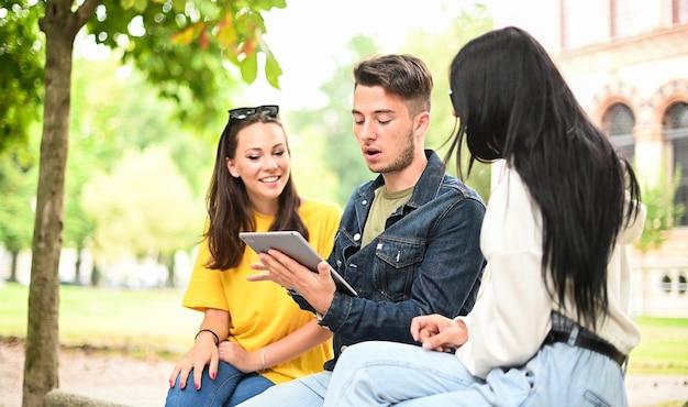 Tre studenti che studiano insieme a una tavoletta digitale seduti su una panchina all'aperto