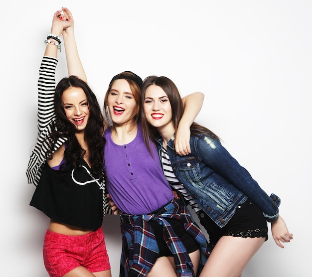 Tre migliori amiche di ragazze alla moda hipster. stare insieme e divertirsi. guardando in avanti. su grigio.