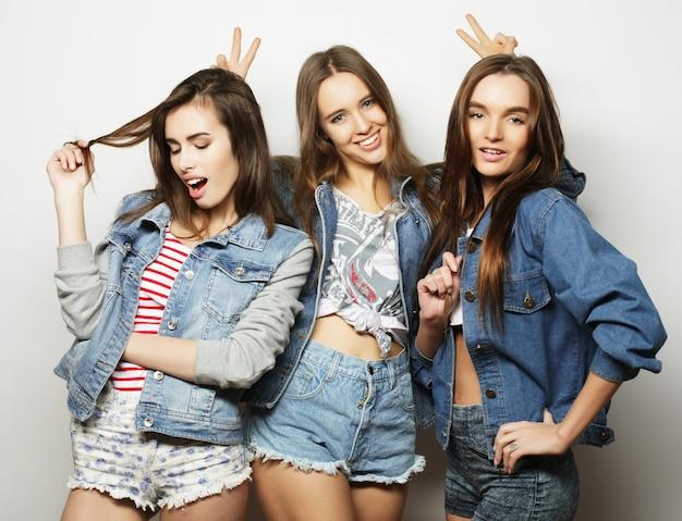 Tre migliori amiche di ragazze alla moda hipster su bianco