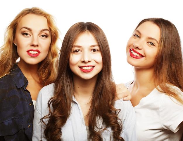 Tre ragazze alla moda sexy hipster migliori amiche. stare insieme e divertirsi. su sfondo grigio.