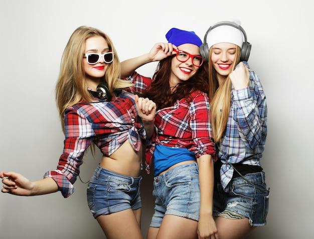 Tre migliori amiche di ragazze hipster sexy alla moda. stare insieme e divertirsi. su sfondo grigio.