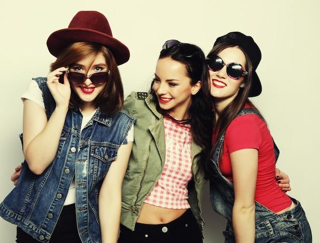 Tre ragazze alla moda sexy hipster migliori amiche. stare insieme e divertirsi. guardando la fotocamera. su sfondo grigio.