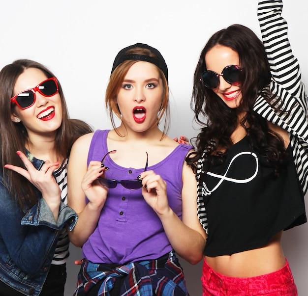 Tre ragazze alla moda sexy hipster migliori amiche. stare insieme e divertirsi. guardando la fotocamera. su sfondo grigio. Foto Premium
