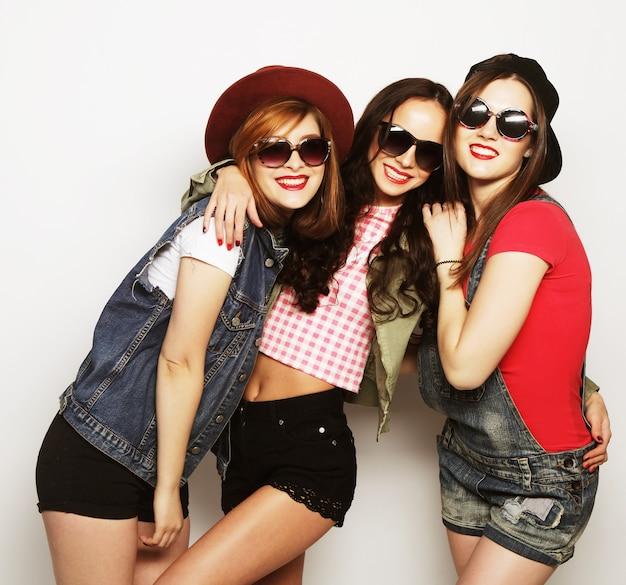 Tre migliori amiche di ragazze hipster sexy alla moda. stare insieme e divertirsi. guardando la fotocamera. su sfondo grigio.