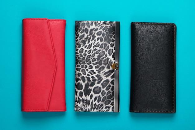 Tre eleganti portafogli sul blu. minimalismo della moda.