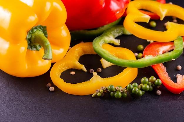 Tre peperoni dolci su uno sfondo di legno, cucinando insalata di verdure
