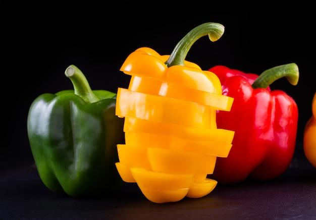 Tre peperoni dolci su un fondo di legno,