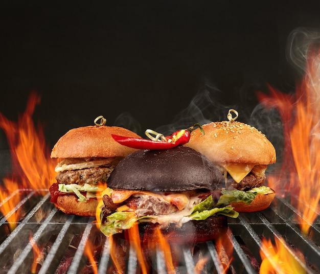 Tre gustosi hamburger con carne di manzo, lattuga, formaggio e peperoncino piccante arrostiti su un barbecue portatile in metallo griglia per barbecue con fuoco ardente e carbone di legna. concetto di cottura. primo piano, copia spazio
