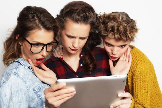 Tre amici di ragazze adolescenti che prendono selfie con tablet digitale, studio girato su sfondo grigio