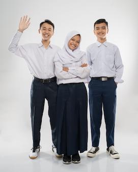Tre adolescenti in uniforme della scuola media stanno sorridendo alla telecamera mentre salutano con un han...