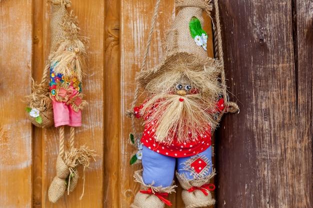 Tre bambole tessili in magliette rosse e bianche con piccole scatole di legno.