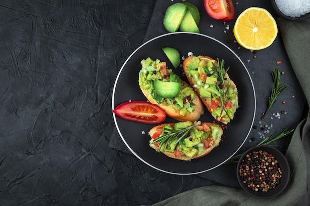 Tre toast con guacamole e rosmarino su sfondo nero.