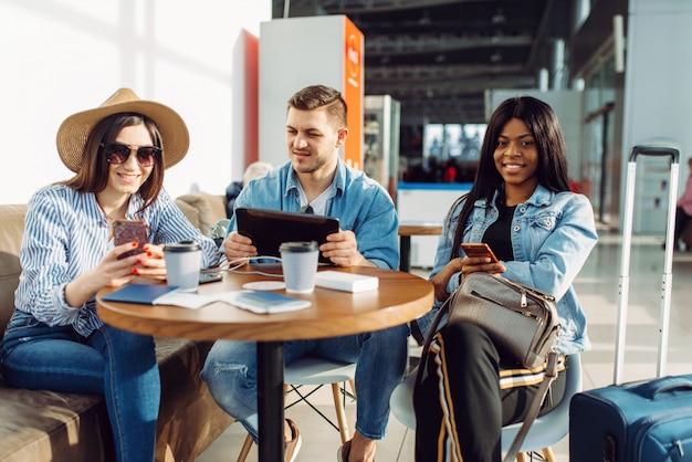 Tre turisti con telefoni e laptop al tavolo in attesa della partenza in aeroporto.