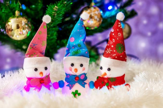 Tre pupazzi di neve giocattolo vicino all'albero di natale buona compagnia divertente