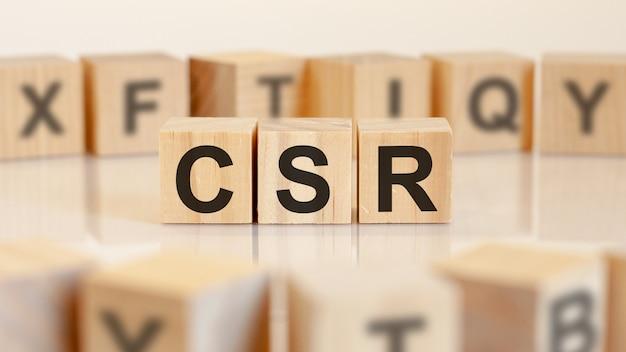 Tre blocchi di legno giocattolo con lettere csr su un tavolo con sfondo chiaro, messa a fuoco selettiva. csr - abbreviazione di responsabilità sociale d'impresa