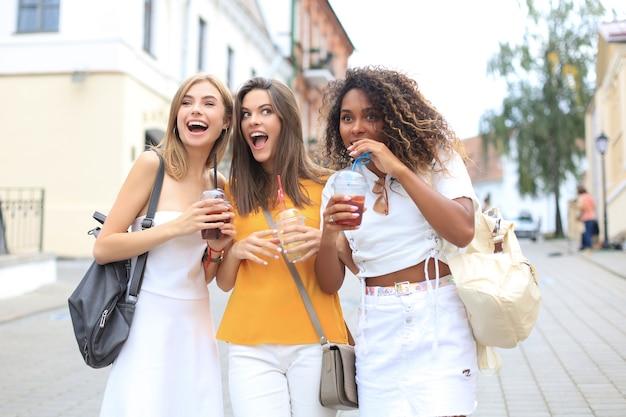 Tre ragazze cool hipster alla moda, amici bevono cocktail sullo sfondo urbano della città.