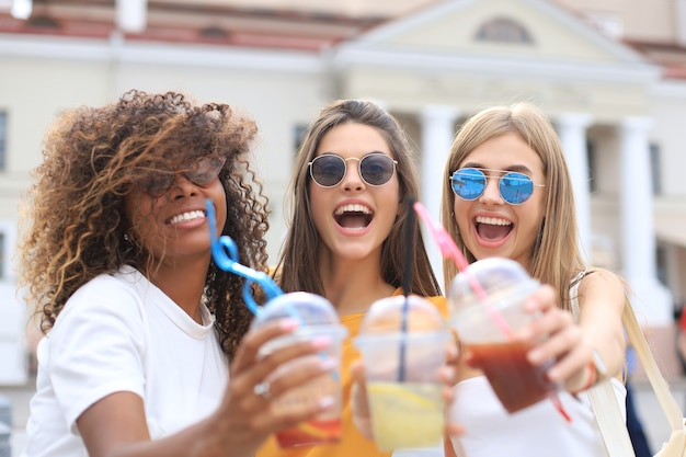 Tre ragazze alla moda cool hipster, amici bevono cocktail sullo sfondo urbano della città.