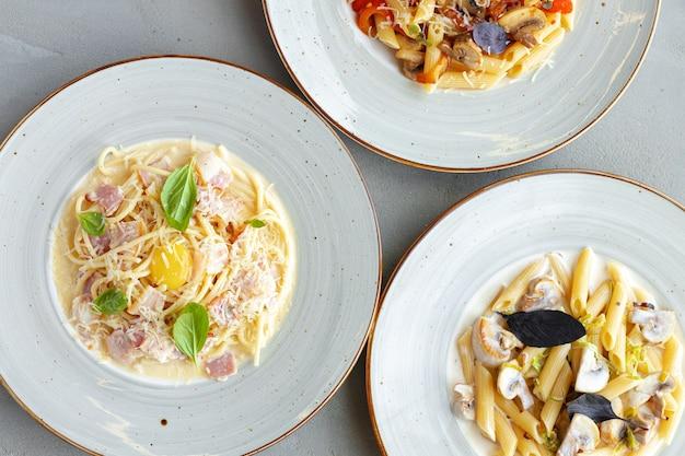 Tre tipi di pasta serviti sulla vista superiore del tavolo grigio