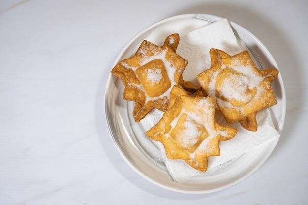 Tre tipici cupcakes di patate dolci e mele cotogne fritte in un piatto di terracotta su un piano di lavoro in marmo. concetto di cucina etnica o regionale. vista dall'alto