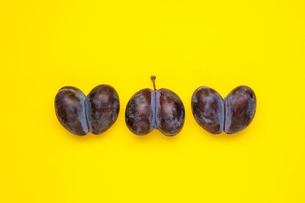 Tre brutte prugne a forma di cuore su sfondo giallo le brutte verdure e frutta sono adatte a foo