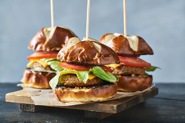 Tre cursori per hamburger vegani con panini pretzel