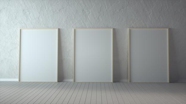 Tre poster con cornice in legno verticale sul pavimento in legno con muro bianco.