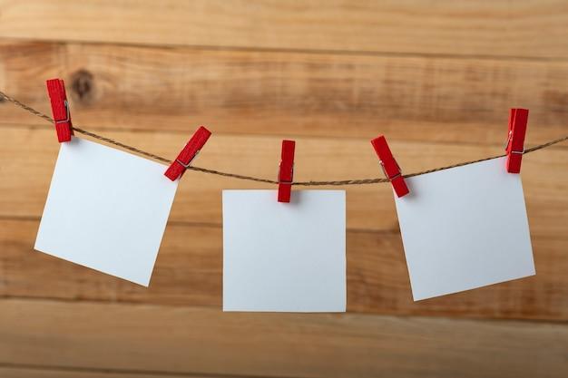 Tre biglietti da visita in bianco bianchi appesi con mollette. superficie in legno. copia spazio.