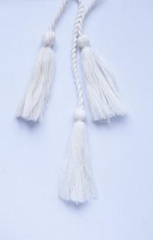 Tre pennelli bianchi decorativi su superficie grigia