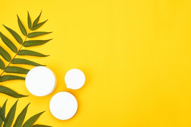Tre barattoli cosmetici bianchi contro uno sfondo giallo, copyspace, flatley