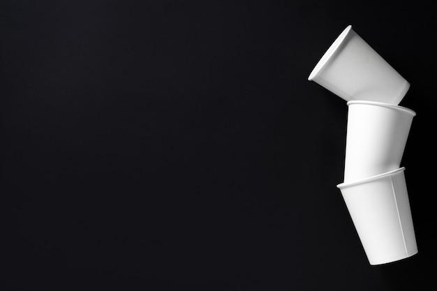 Tre tazze di caffè di carta bianca su sfondo nero. posto per il testo. vista dall'alto.