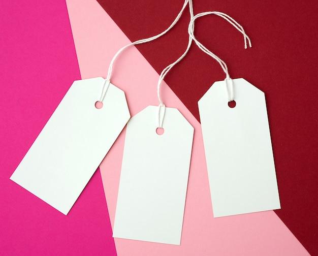Tre etichette rettangolari di carta bianca su una corda su uno sfondo colorato
