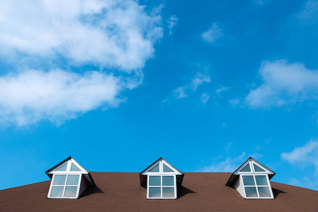 Tre finestre su un tetto di casa con un bellissimo cielo e nuvole sullo sfondo