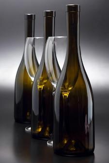 Tre bottiglie di vino e due bicchieri di vino vuoti si chiudono